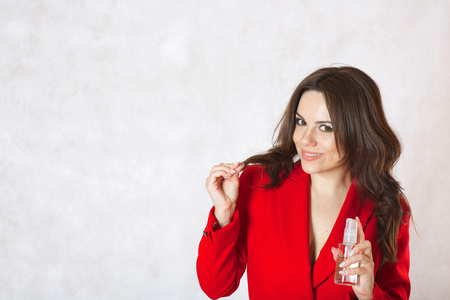 between 30 and 40 years: A young woman between 30 and 40 years old dressed in a classical red jacket shows a glass bottle with hair oil.