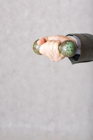 age 60: A dumbbell in the hand of a man in a classical costume. Closeup Stock Photo