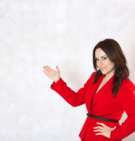 30 to 40 years: A young woman between 30 and 40 years old dressed in a classical red jacket shows a solution Stock Photo