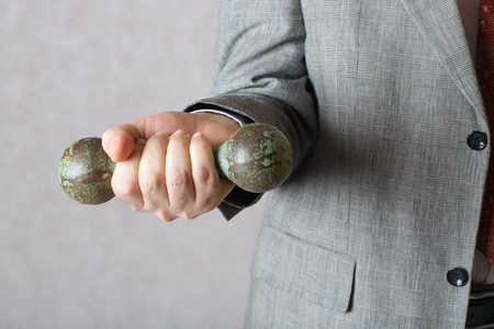 50 to 60 years: A dumbbell in the hand of a man in a classical costume. Closeup Stock Photo