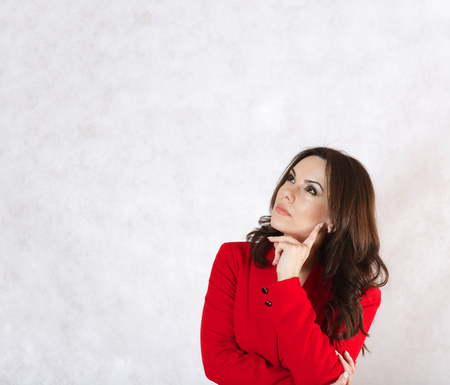 30 years old woman: A young woman between 30 and 40 years old dressed in a classical red jacket is reflecting on something
