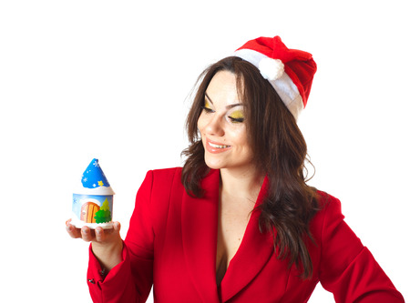 30 to 40 years: A young woman between 30 and 40 years old dressed in a classical red jacket and a santa claus hat on a white background, keeps a small wooden winter house.