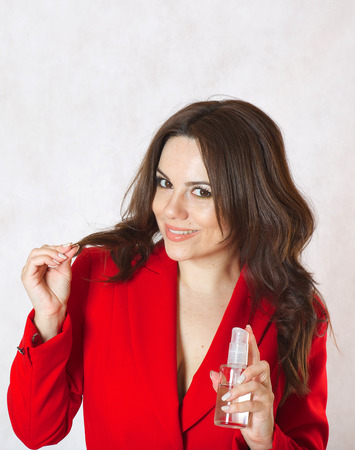 30 to 40 years: A young woman between 30 and 40 years old dressed in a classical red jacket shows a glass bottle with hair oil.