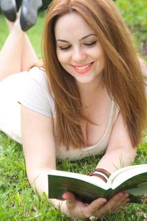 thirties: A young attractive woman in her thirties is reading a book.