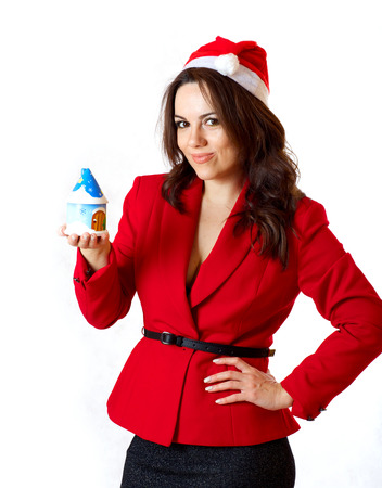 winter  house: A young woman between 30 and 40 years old dressed in a classical red jacket and a santa claus hat on a white background, keeps a small wooden winter house.