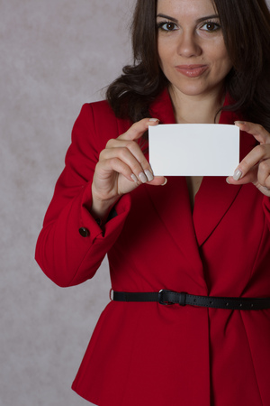 between 30 and 40 years: A young woman between 30 and 40 years old dressed in a classical red jacket keeps a white card with free space for a text.