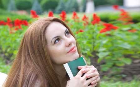 thirties: A young attractive woman in her thirties is dreaming about something keeping a read book. Stock Photo