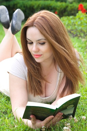 starring: A young attractive woman in her thirties is reading a book lying in the grass