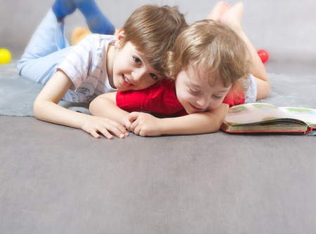 poems: Two brothers 6 and 3 years old are hugging each other on a gray carpet. Free space for a text. Stock Photo