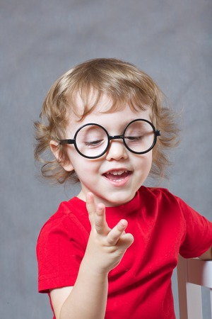 three fingers: A child of 3 years old  with long hair shows his three fingers on a gray background