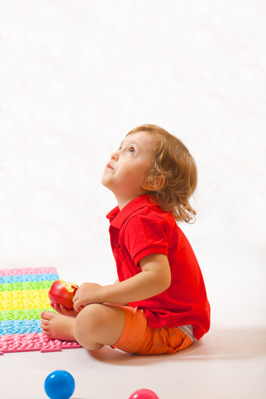 A boy of three years old  is gazing something up eating an apple. Free space for a text