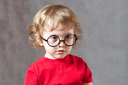 Małe dziecko na szarym tle z uczuciem jest zaskoczony. Wolne miejsce dla tekstu.