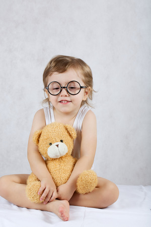 A boy of three years old with a plush teddy bear sitting on a white blanket. Free space for a text. Stock Photo