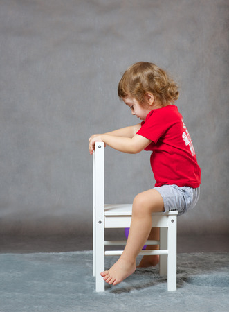 three years old: A boy of three years old is riding a chair as if it were a horse. Free space for a text. Stock Photo