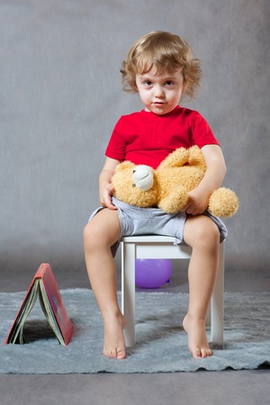 poems: A child of 3 years old  with long hair is sitting on a white chair with a teddy bear.A closed book of poems is near to the chair  on a gray background