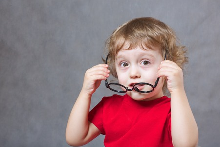 occlusion: A child of 3 years old  with long hair tries to put on  eye glasses. Gray background  Free space for a text.
