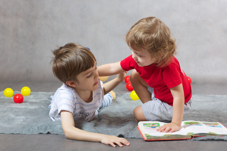 poems: Two brothers 6 and 3 years old are reading the book on a gray background Stock Photo