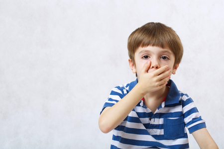 six years: A boy of six years old  covers his mouth on a white background. Free space for a text.