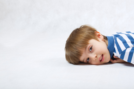 gesticulation: A boy of six years old leant his face at a white background  . Free space for a text.