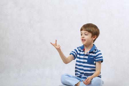 gesticulation: A boy of six years old is counting on a white background  . Free space for a text.