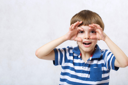shortsightedness: A boy of six years old imitates watching binocular on a white background  . Free space for a text.