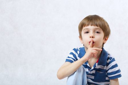 six years: A boy of six years old  asks for silence on a white background  . Free space for a text.