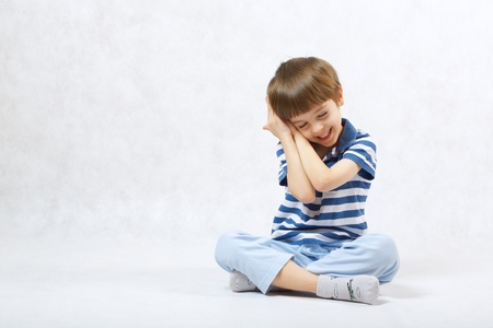 gesticulation: A boy of six years old show that he wants to sleep. White background  . Free space for a text.