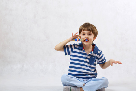 six years: A boy of six years old is cleaning his teeth with tooth brush on a white background Stock Photo