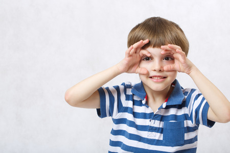 A boy of six years old is imitating watching binocular  on a white background  . Free space for a text.