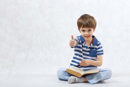 six years: A boy of six years old is reading a book on a white background