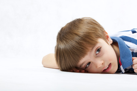 six years: A boy of six years old  leant his face at  a white background  . Free space for a text.