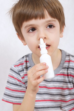 six years: A boy of six years old  sprays nasal spray in one of a nostril.White background