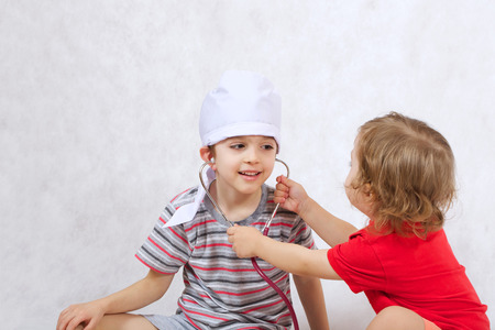 Two brothers of six and three years old are playing in doctor and a patient. White background