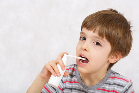 six years: A boy of six years sprays medicine in his throat Stock Photo