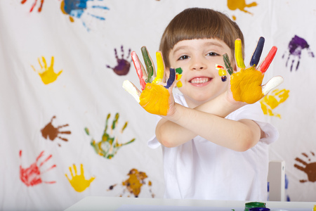 pedagogy: Boy of seven years old with painted palms. Closeup Stock Photo