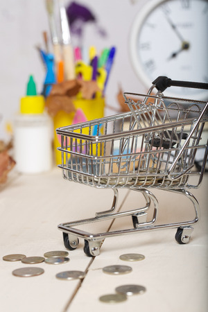 pedagogical: Expenses for preparation to school. Mini shopping cart with coins. Back to school stationery in the background