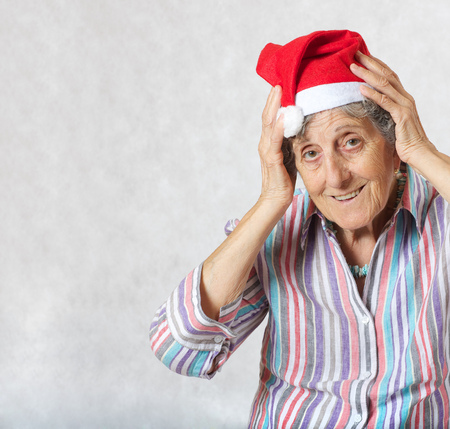 Old woman between 70 and 80 years old in the hat of a santa claus