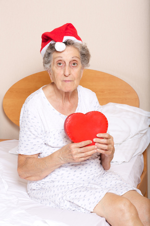 Old woman between 70 and 80 years old dressed in santa hat with red heart in her hands Stock Photo