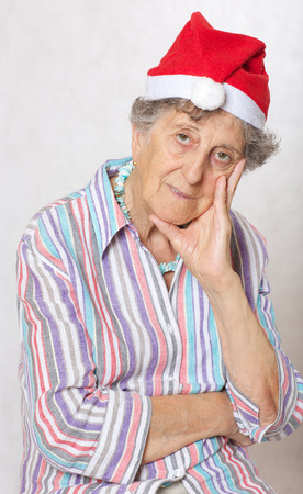 80 years: Old woman between 70 and 80 years old in the hat of a santa claus