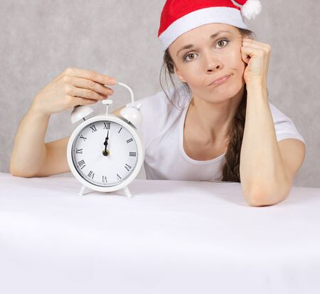 Young woman dressed in Santas hat with vintage alarm clock. Closeup Stock Photo