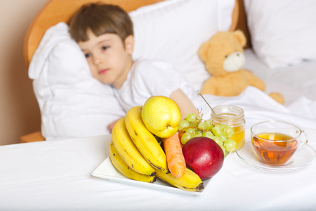 Fruits,tea and honey on the table in front of a sick child