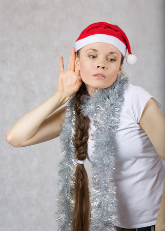Young lady in a Santas hatis listening to someones conversation. Free space for a text. Zdjęcie Seryjne