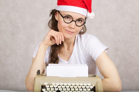 Młoda dama w Santa Claus kapelusz w pobliżu maszyny do pisania. Zdjęcie Seryjne