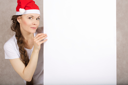 Young lady between 30 and 40 years in Santa Claus hat