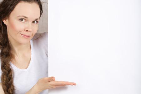 Młoda dama od 30 do 40 lat pokazuje coś na białej kartce papieru.