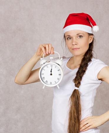 Młoda kobieta ubierał w Santas kapeluszu z rocznika budzikiem. Zbliżenie