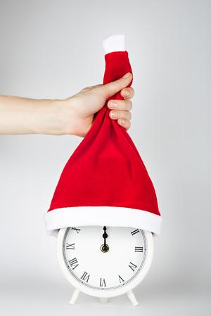Biały rocznik budzik na szarym tle w Święty Mikołaj kapeluszu. Zdjęcie Seryjne