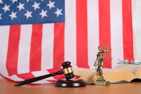 Statue of Themis and judges gavel on a table. Flag of United States of America in the background.