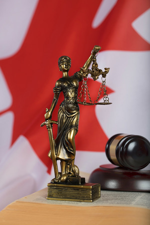 Statue of Themis and judges gavel on a book. Flag of Canada in the background. Closeup