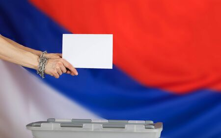 Female hands fastened by metal chain cast ballot paper in the ballot box. Russian flag in the background. Stock Photo